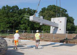 Die schweren Bauteile werden mit Sattelzügen angeliefert und müssen mit einem Kran abgeladen und an der richtigen Position auf der Baustelle platziert werden.